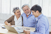 Happy retired Asian senior elderly couple consult with personal financial advisor or real estate agent. Retirement investment planning with professional counseling. Home loan and mortgage concept
