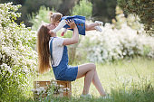 Mother and one year old daughter have fun together in a green park in spring