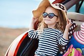 Cute little girl sitting in car trunk loaded with suitcases outdoors near the sea