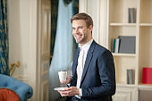 Smiling officially dressed man having a cup of coffee