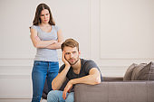 Young woman standing with arms clasped while her husband sitting with depressed look