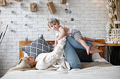 Mother and little daughter have fun and play together in a bright sunny bedroom on a white bed