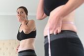 Shocked adult woman measuring waist circumference