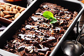 Chocolate icecream in metal tray with mint leaf and almond nuts