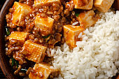 Authentic traditional Chinese food mapo tofu dish with pork and steamed rice closeup