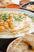 Closeup view at Hummus topped with beans olive oil and green coriander leaves on kitchen table with pita bread