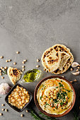 Flat lay view at Hummus in clay dish topped with olive oil, chickpeas and green coriander leaves on stone table served with traditional Pita bread
