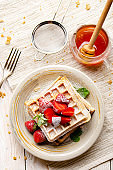 Flat lay view at Belgian waffles served with strawberries and mint leaf dusted with powdered sugar