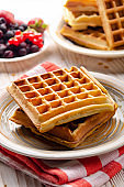 Belgian waffles served with butter banana mint leaf and syrup