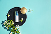 Face cream, elixir for beauty flat lay on a blue background with flowers. Concept of natural organic cosmetics. Minimalism