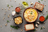 Hummus topped with chickpeas, olive oil and green coriander leaves on stone table with different spices aside. Flat lay