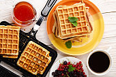 Flat lay view at Belgian Waffles on cast skillet and stacked on plate with syrup berries and coffee aside