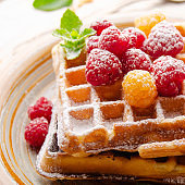 Belgian waffles served with raspberries and mint leaf dusted with powdered sugar on white wooden kitchen table