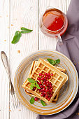 Flat lay view at Belgian waffles served with red currants and mint leaf on white wooden kitchen table with syrup aside