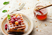 Belgian waffles served with raspberries and mint leaf dusted with powdered sugar on white wooden kitchen table with syrup aside