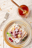 Flat lay view at Belgian waffles served with raspberries and mint leaf dusted with powdered sugar