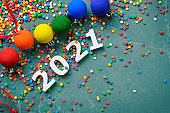 White numbers 2021 with color sugar sprinkles on stone table with color balls