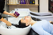 Gorgeous cheerful young woman enjoying head massage while getting her hair mask by a professional hairdresser
