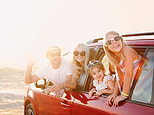 Happy smiling family with daughters in the car with sea background