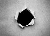 A hole in vintage paper with torn edges close-up with a black isolated background inside.