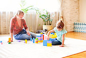 Happy grandmother playing with granddaughter on floor