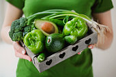 Crop woman with box of green vegetables