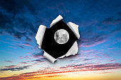 A hole in the sunset sky with torn edges, as if on paper, overlooking the night sky with a full moon and stars. The concept of global climate change on Earth, global warming, a hole in space and time.