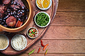 Feijoada. Traditional Brazilian food. Ceramic bowl isolated on rustic wooden background. Top view.
