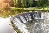 Semicircular spillway of hydroelectric power station with boiling water in sunlight in green Park area