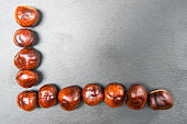 Fresh chestnut fruit scattered on stone background. Top view. With your place for text