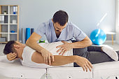 Chiropractor, osteopath, physiotherapist or manual therapist working with male patient