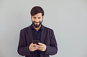 Positive guy in a jacket is typing text in a mobile smiling with on a gray background.