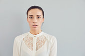 Puzzled insecure woman in white shirt on a gray background. Expression of emotion
