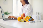 Fruit, measuring tape and glass of water placed on desk against blurred dietitian working on laptop