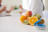 Fresh fruit and measuring tape on desk against blurred dietitian giving consultation to patient