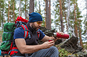 Tourist pours tea from a thermos in the forest.
