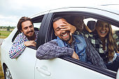A group of happy friends are driving in a car.