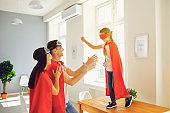 Happy family of superheroes playing in a room indoors.
