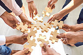 Company employees playing game and joining pieces of jigsaw puzzle during team building activity