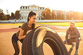 Athletic girl pushes a tire in the stadium at sunset.