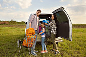 Happy parents and daughter travelers take backpacks from a car for hiking in nature.
