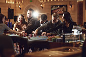 Group of friends bet at the roulette table in a casino.