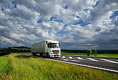 White truck driving on the asphalt road in a rural landscape
