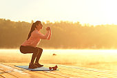 A young girl in training does squats at sunrise by the lake in autumn.