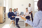 Group of office workers sitting and listening to colleague making presentation in office