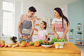 Happy family with kid preparing fresh vegetables on the table in the kitchen.