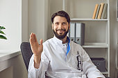 Portrait of friendly doctor gesturing patient during online video consultation. Telemedicine concept