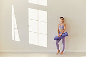 Yoga woman. Happy sport woman with yoga mat on white wall in a bright room.