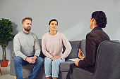 Family psychologist. Female psychologist at a psychotherapy session with family in the office.