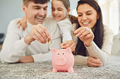 Happy family saves money in a piggy bank pig.